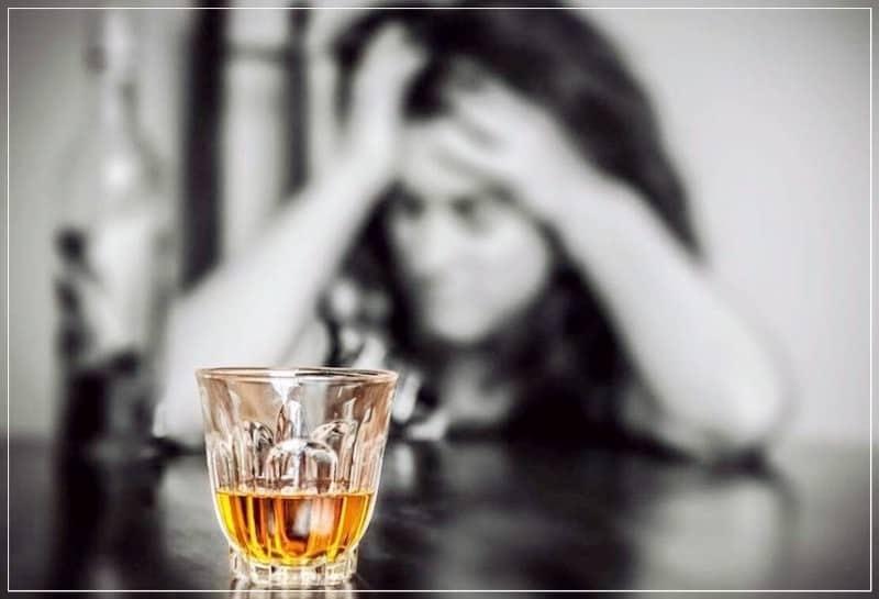 стакан виски перед женщиной