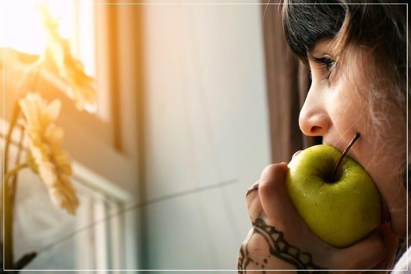 девочка есть яблоко и смотрит в окно