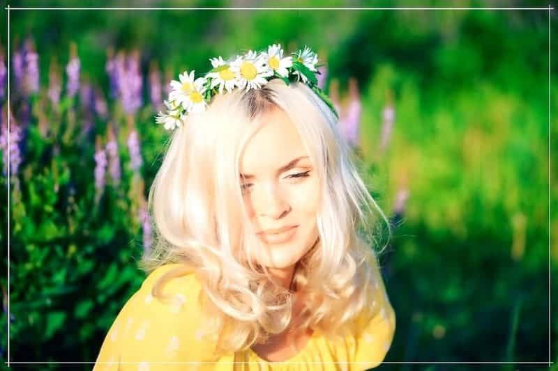 у блондинки блестящие волосы и венок из ромашек