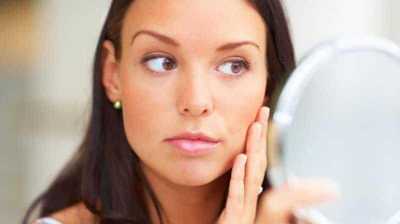 красивая девушка смотрит в зеркало