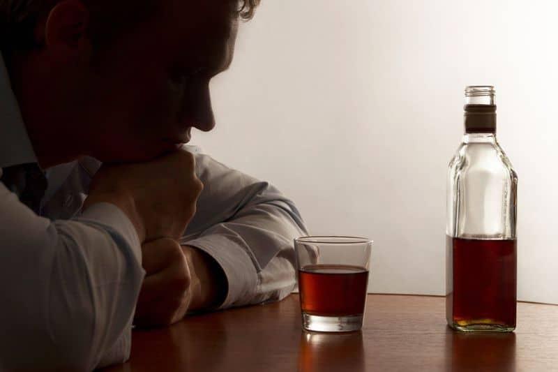 мужчина смотрит на алкоголь