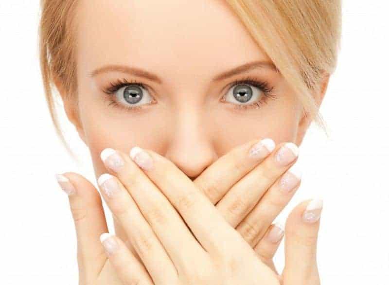 девушка прикрывает руками рот