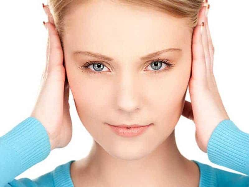 девушка прикрывает уши