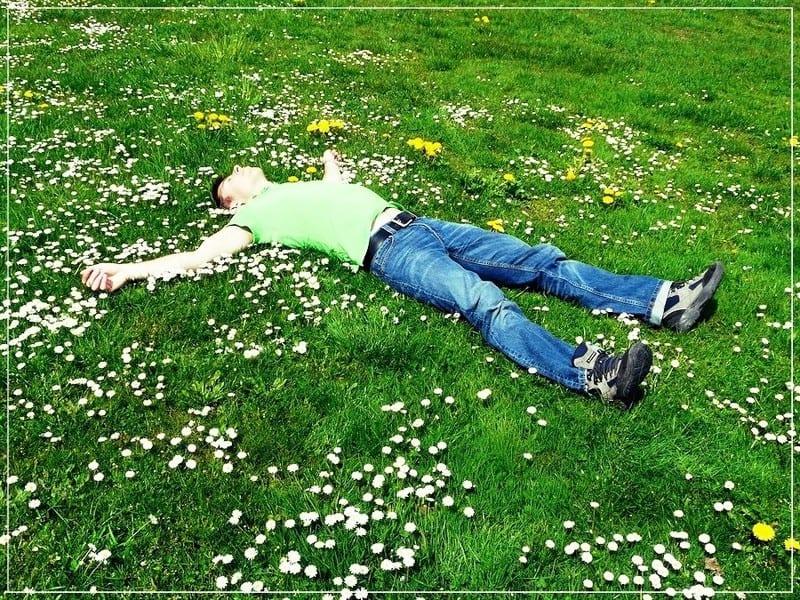 человек лежит на зелёной траве раскинув руки